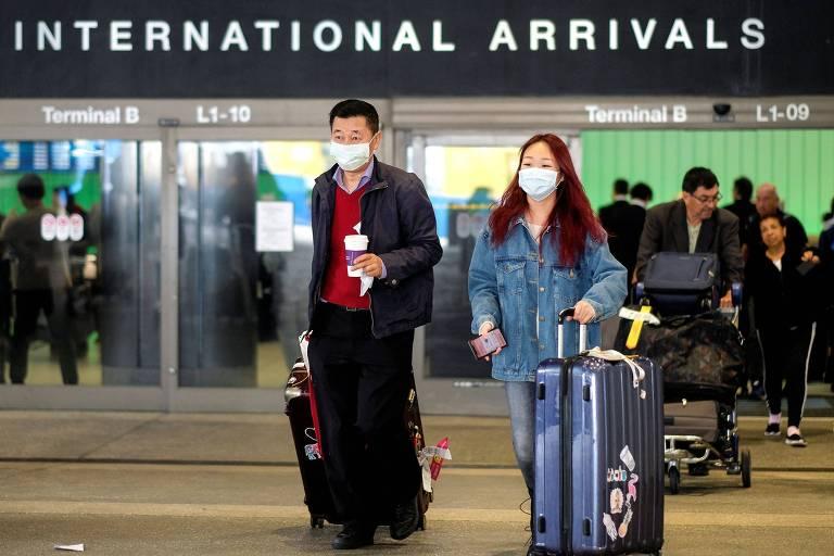 Passageiros chegam ao aeroporto de Los Angeles de voo de Xangai, na China