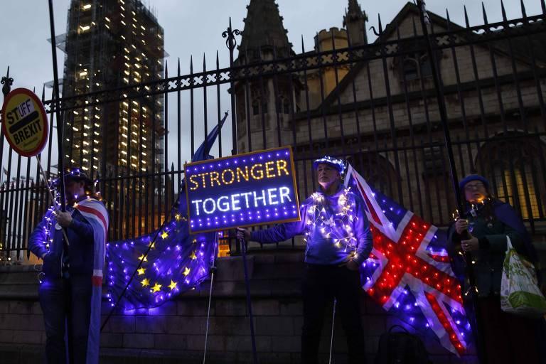 Com cartazes iluminados e bandeiras do Reino Unido e da União Europeia, manifestantes antibrexit protestam em frente ao Parlamento britânico, em Londres
