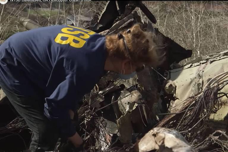 Investigadora do Conselho Nacional de Segurança nos Transportes (NTSB, na sigla em inglês) observa destroços do helicóptero de Kobe Bryant