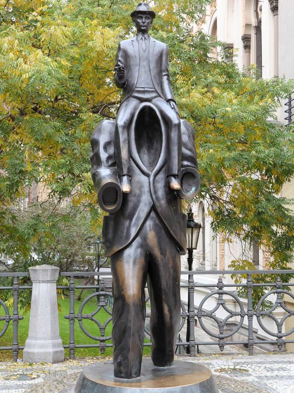 Estátua de bronze em Praga, de quatro metros de altura, em homenagem a Kafka, na qual o escritor é representado sentado sobre um homem sem braços e cabeça