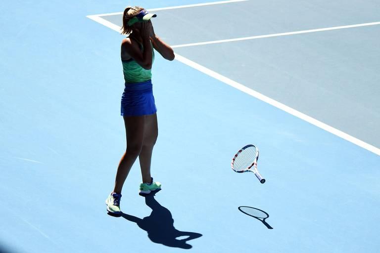 Raquete de Sofia Kenin jogada no chão enquanto ela leva as mãos ao rosto