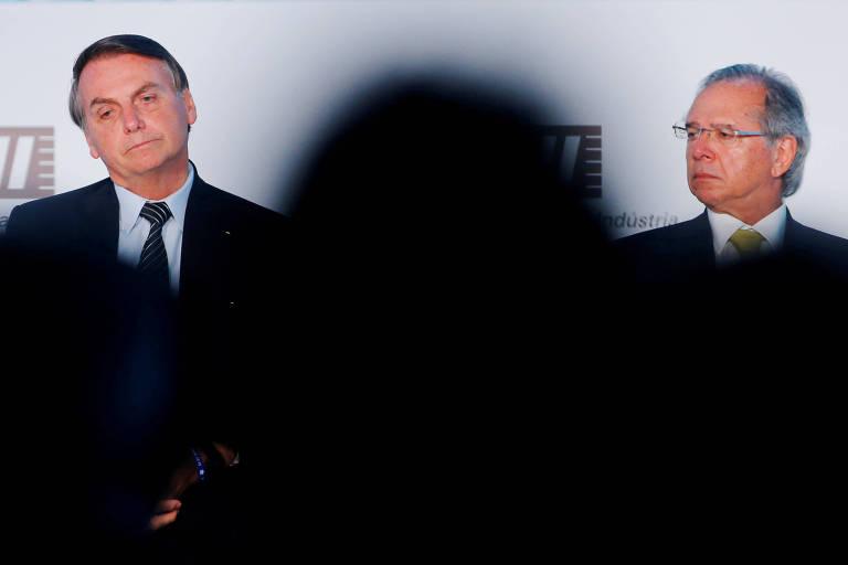 Bolsonaro aparece à esquerda, e Guedes, à direita. Entre os dois há a sombra de uma pessoa