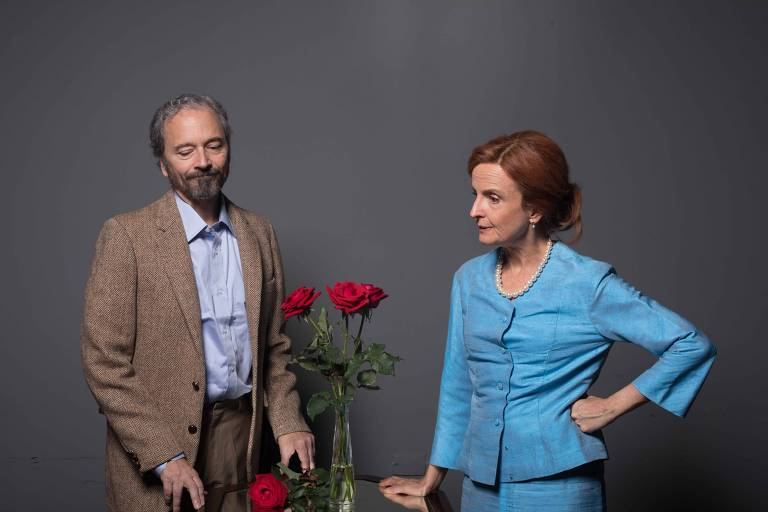 Homem e mulher de pé em volta de uma mesa