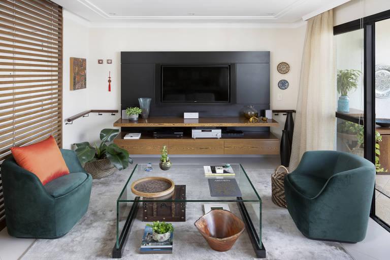 Sala com sofás e corrimão de madeira na parede