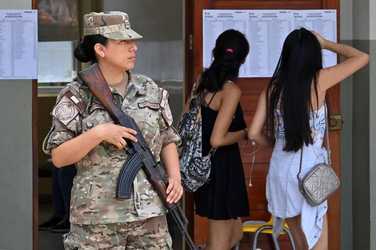 Em Lima, soldada do Exército do Peru vigia local de votação nas eleições legislativas no país
