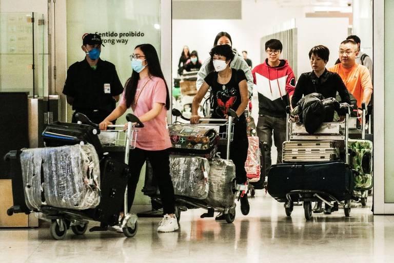Passageiros com máscaras no Aeroporto Internacional de São Paulo, em Guarulho
