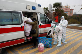 Hospital staff in protective garments pick up a leukaemia patient who arrived from the Hubei province exclusion zone at a checkpoint at the Jiujiang Yangtze River Bridge in Jiujiang