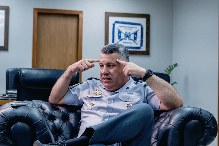 Marcelo Vieira Salles fotografado enquanto fala na entrevista. Olha para o lado esquerdo, para seu interlocutor, que não aparece na foto. Tem os dois dedos indicadores pressionados contra a testa. Usa farda da polícia militar de São Paulo, na cor azul claro. Está sentado em um sofá de couro preto.