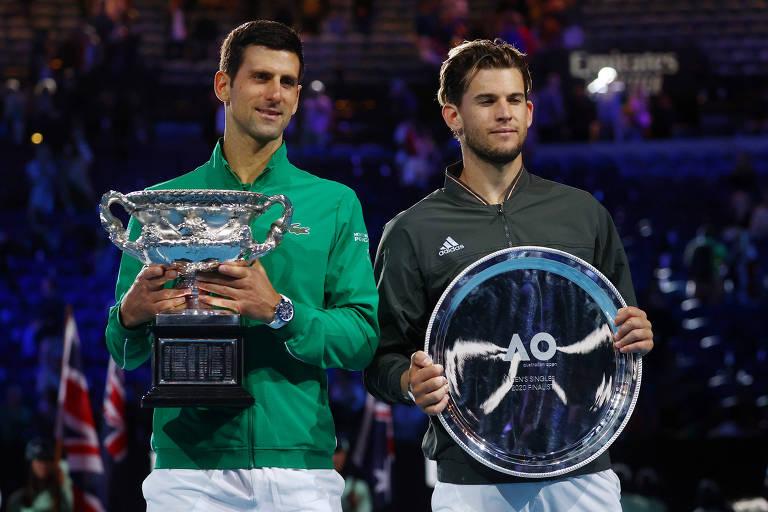 Djokovic e Dominic Thiem posam com os respectivos troféus após a decisão do Grand Slam australiano