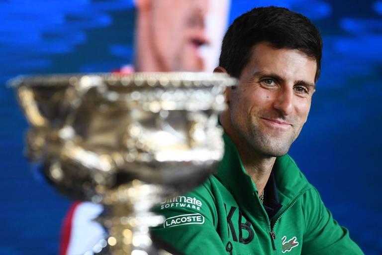 Novak Djokovic, com o troféu de campeão ao lado, sorri após a conquista do Australian Open