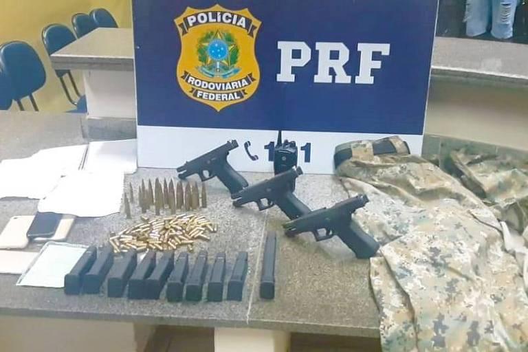 Armas, munição, celulares e roupa camuflada sobre mesa na qual também está o logo e as iniciais da Policia Rodoviária Federal
