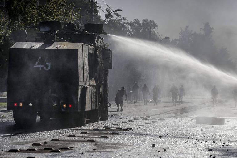 Polícia joga água em torcedores do Universidad de Chile durante confrontos nas redondezas do Estádio Nacional, em Santiago