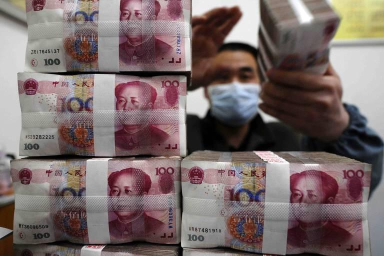Na foto, várias cédulas de iuans amarradas e empilhadas. Atrás, um trabalhador do banco central chinês conta cédulas de iuan com uma máscara no rosto.