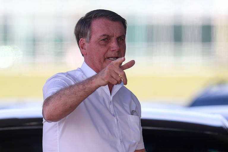 Retrato de jair Bolsonaro, que veste uma camisa social branca de manga curta; o presidente gesticula com a mão apontando para os fotógrafos