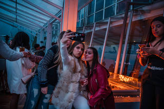Teens mug for a selfie during a 17-year-old's birthday party at a bar in Caracas, Venezuela, Dec. 20, 2019. (Adriana Loureiro Fernandez/The New York Times)