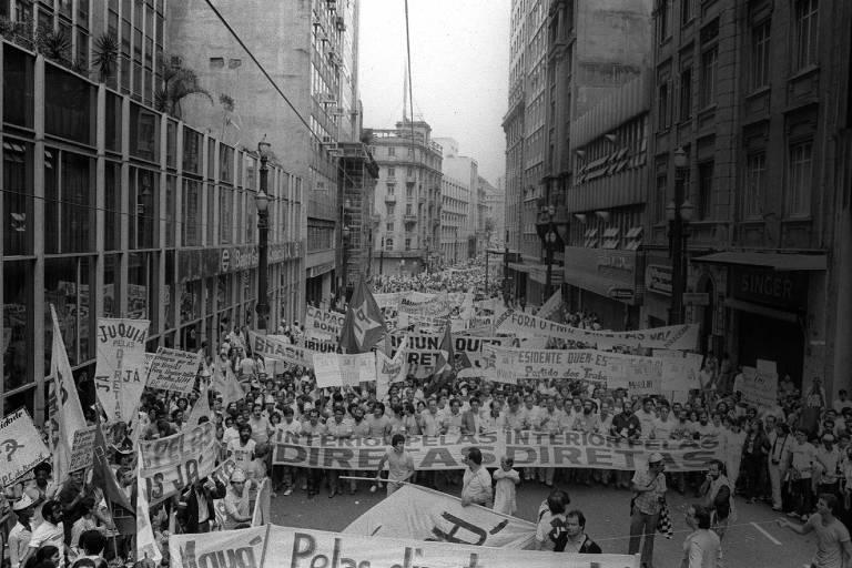 """Uma multidão marcha segurando cartazes e faixas com dizeres como """"Diretas Já"""""""
