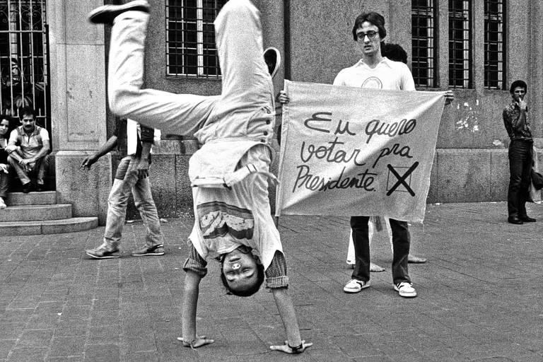 """Um jovem segura um cartaz em que se lê """"Eu quero votar para presidente""""  e outro, a frente, planta uma bananeira"""