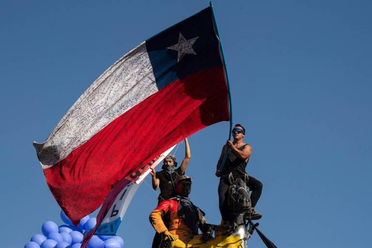 Manifestante agita bandeira do Chile durante protesto em Santiago