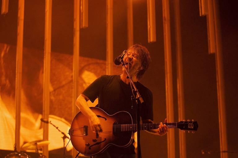 homem em cima do palco tocando violão