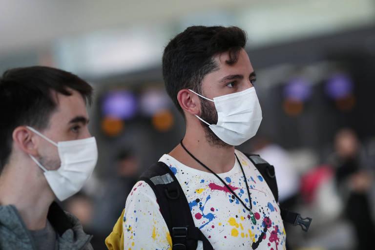 Pessoas no aeroporto de Guarulhos, em São Paulo, usam máscaras para tentar evitar contato com o coronavírus chinês