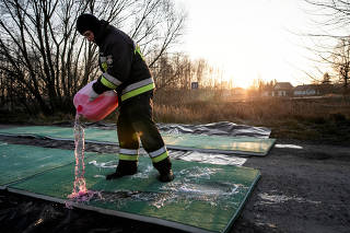 Fireman pours disinfecting liquid on the road in Stary Uscimow, where the bird flu virus was discovered