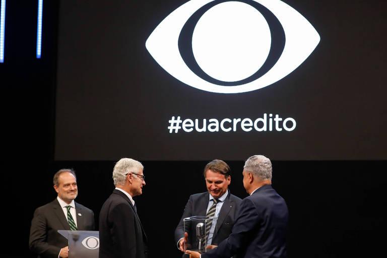"""Bolsonaro recebe caixa em acrílico com um objeto dentro das mãos de Saad; acima, há um painel com a logomarca da Band e a hashtag """"#euacredito"""""""