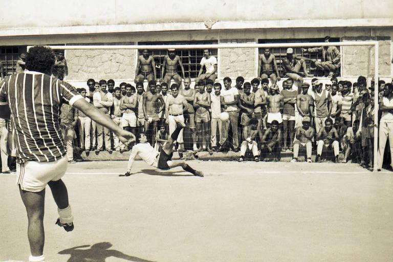 Vários homens sem camisa assistem atrás do gol um detento bater um pênalti. O goleiro está no chão.