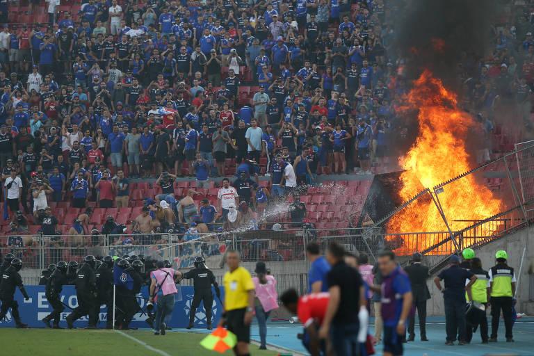 Policiais tentam apagar fogo colocado na arquibancada por torcedores chilenos na partida entre Universidad de Chile e Internacional, pela Libertadores