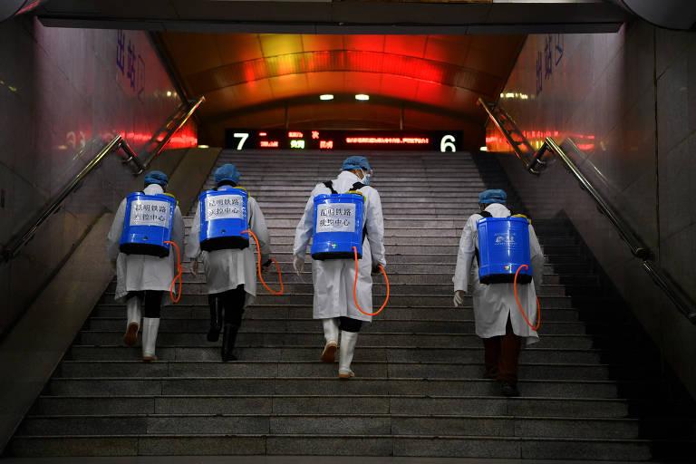 Retrato de quatro trabalhadores vestindo branco, botas brancas e touca azul claro; os trabalhadores sobem escadas e carregam uma espécie de mochila com produtos para desinfetar