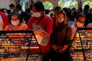 Filipino Catholics pray over lit candles wearing protective masks following confirmed cases of coronavirus in the country, at the National Shrine of Our Mother of Perpetual Help, Paranaque City