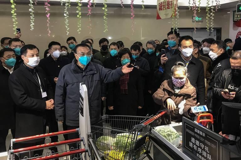 O premiê chinês Li Keqiang (centro) fala com residentes de Wuhan, cidade epicentro da epidemia de coronavírus