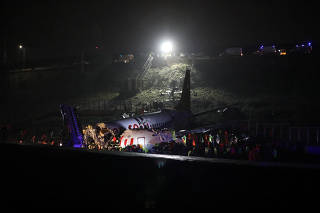 Firefighters and rescue teams are seen next to the wreckage of a plane after it crashed at Sabiha Gokcen airport in Istanbul