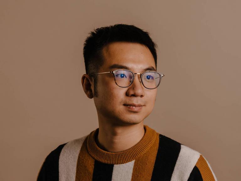 Retrato de Peter Chen; ele usa óculos e veste uma camisa listrada na vertical nas cores branco, preto e dourado