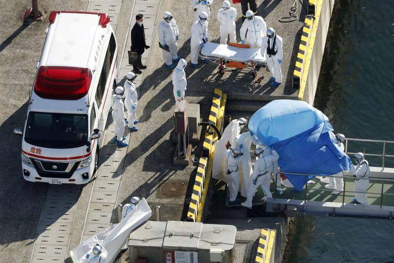Oficiais usando roupa especial levam uma pessoa que está debaixo de um lençol azul para uma base policial de Yokohama, após apresentar sintomas do coronavírus enquanto estava a bordo do navio Diamond Princess