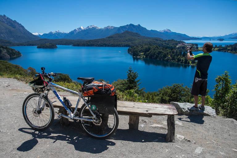 Homem com bicicileta tira foto de paisagem com lago e bosques