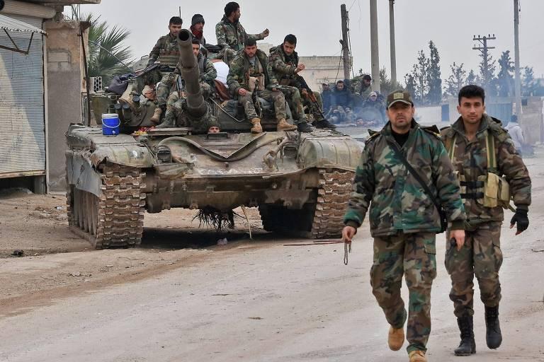 Soldados em cima de um tanque e na rua avançam a noroeste do país, na vila de Tall Touqan, na província rebelde de Idlib