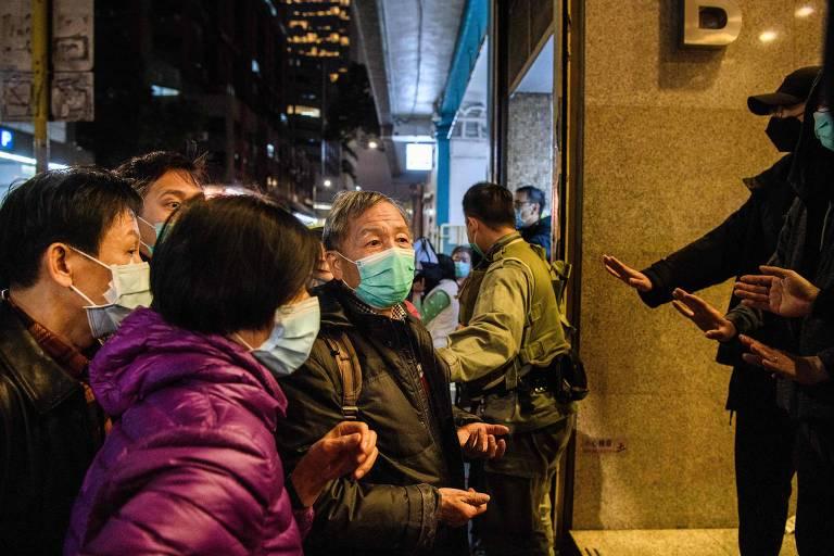Pessoas usando máscaras na cidade chinesa de Wuhan, em frente a uma loja, são impedidas de entrar em uma loja onde os produtos estão esgotados