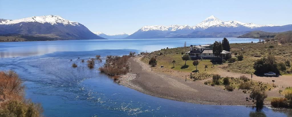 Rio formado por água de lago, com montanhas com neve ao fundo
