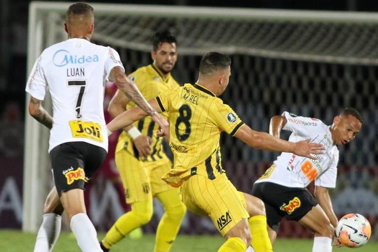 Observado por Luan, Janderson tenta sair da dura marcação dos jogadores do Guaraní, no Paraguai, pela estreia na Libertadores