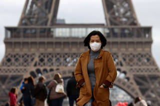 A woman wears a protective mask in light of the coronavirus outbreak in China as she walks at the Trocadero esplanade in front of the Eiffel Tower in Paris