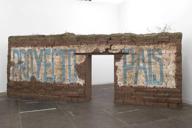 muro de adobe com as palavras 'proyecto' e 'país' pintadas em azul sobre fundo branco