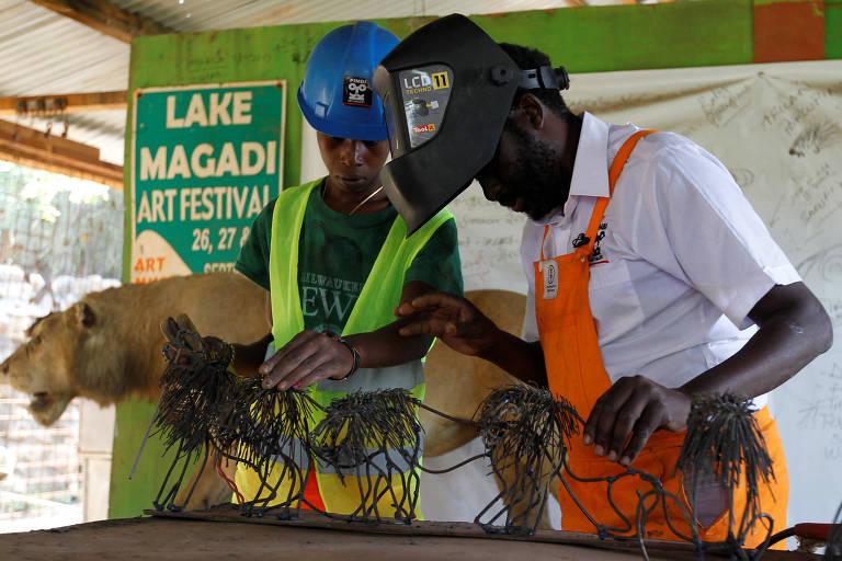 O escultor de metal queniano Kioko Mwitiki e seu aluno, Kelvin Muia, trabalham em uma escultura de metal em seu estúdio de arte em Kajiado, Quênia