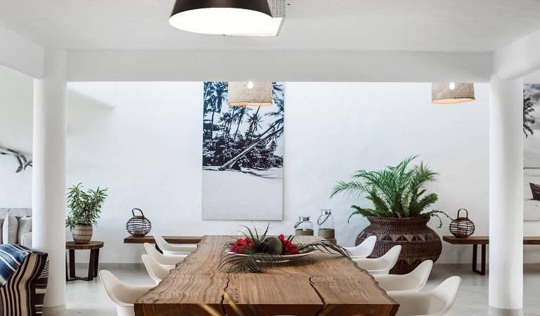 Sala de jantar com paredes e piso brancos e móveis em tons terrosos