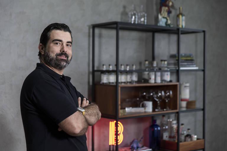 Homem de camisa polo preta de braços cruzados com uma estante com garrafas ao fundo