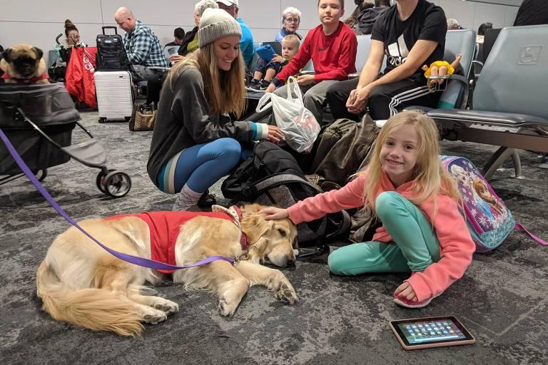 Criança brinca com cachorro no aeroporto internacional de Los Angeles