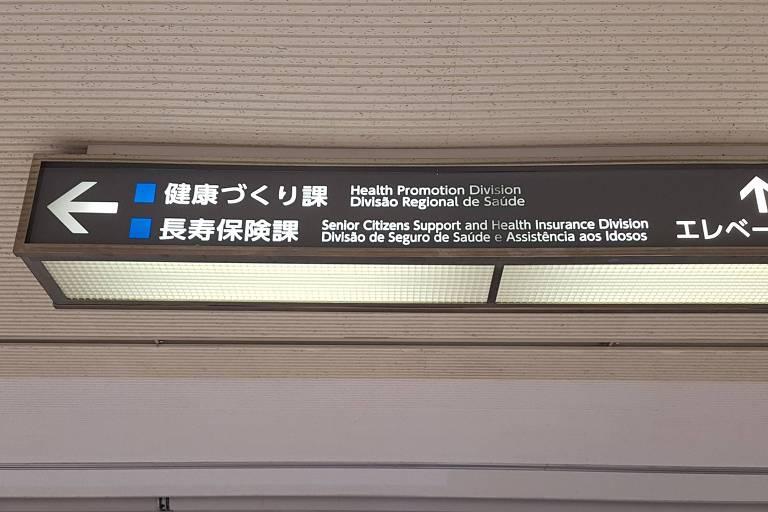 Placa pende de teto com inscrições em português, japonês, inglês e espanhol