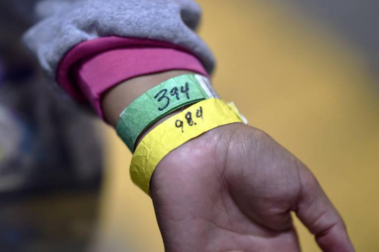 Brasileira deportada mostra as pulseiras colocadas em seu braço pelo ICE; a verde tem número de identificação e a amarela, sua temperatura corporal medida em graus Fahrenheit