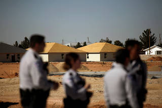 Buildings under construction and to be used as shelters for migrant children are seen in the background as security officers stand still during a protest against the facility, on the outskirts of El Paso, Texas