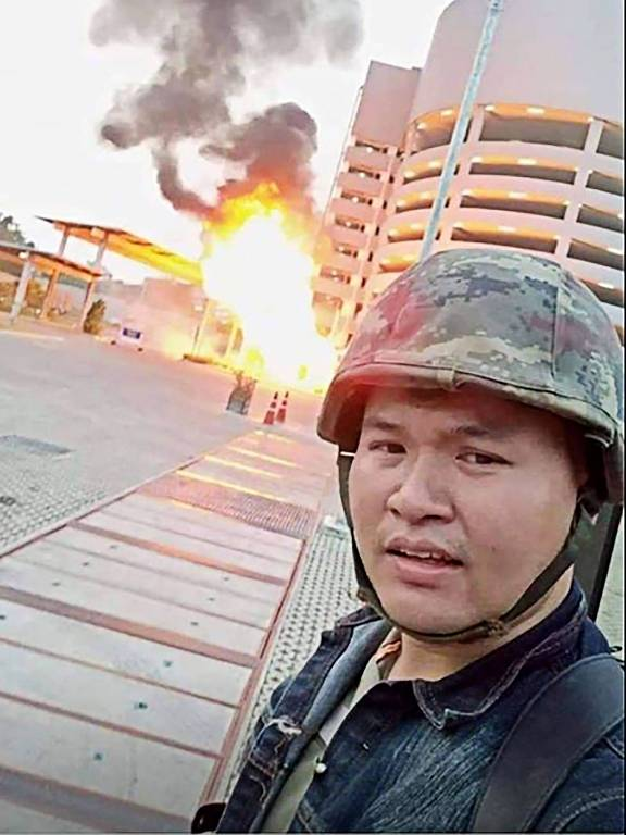 militar em frente a prédio em chamas