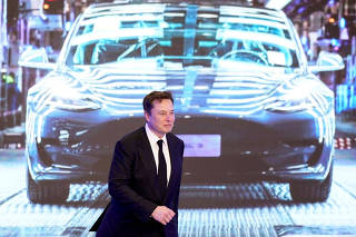 FILE PHOTO: Tesla Inc CEO Elon Musk walks next to a screen showing an image of Tesla Model 3 car during an opening ceremony for Tesla China-made Model Y program in Shanghai, China